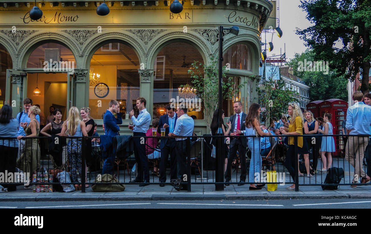 people socialising and drinking at a pub in London in summer - Stock Image