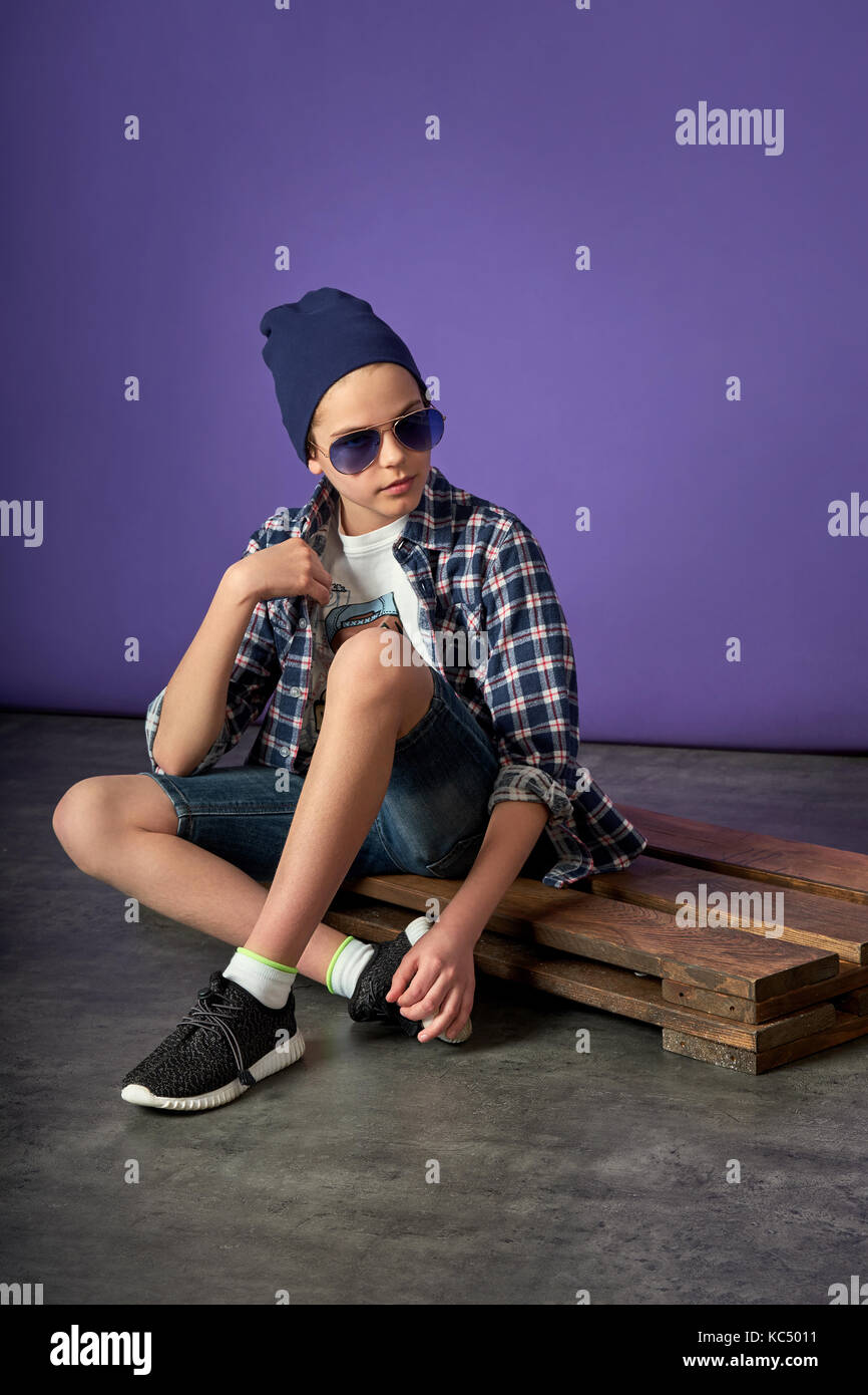Young fashion man boy sitting on the floor. - Stock Image