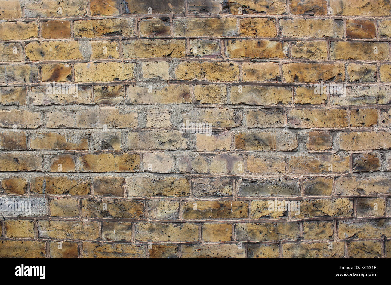 A background of yellow London bricks slightly distressed - Stock Image
