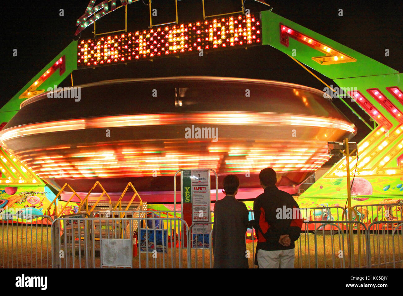 Silhouetted parents watch and wait while their children spin inside aan Amusement Park thrill ride - Stock Image