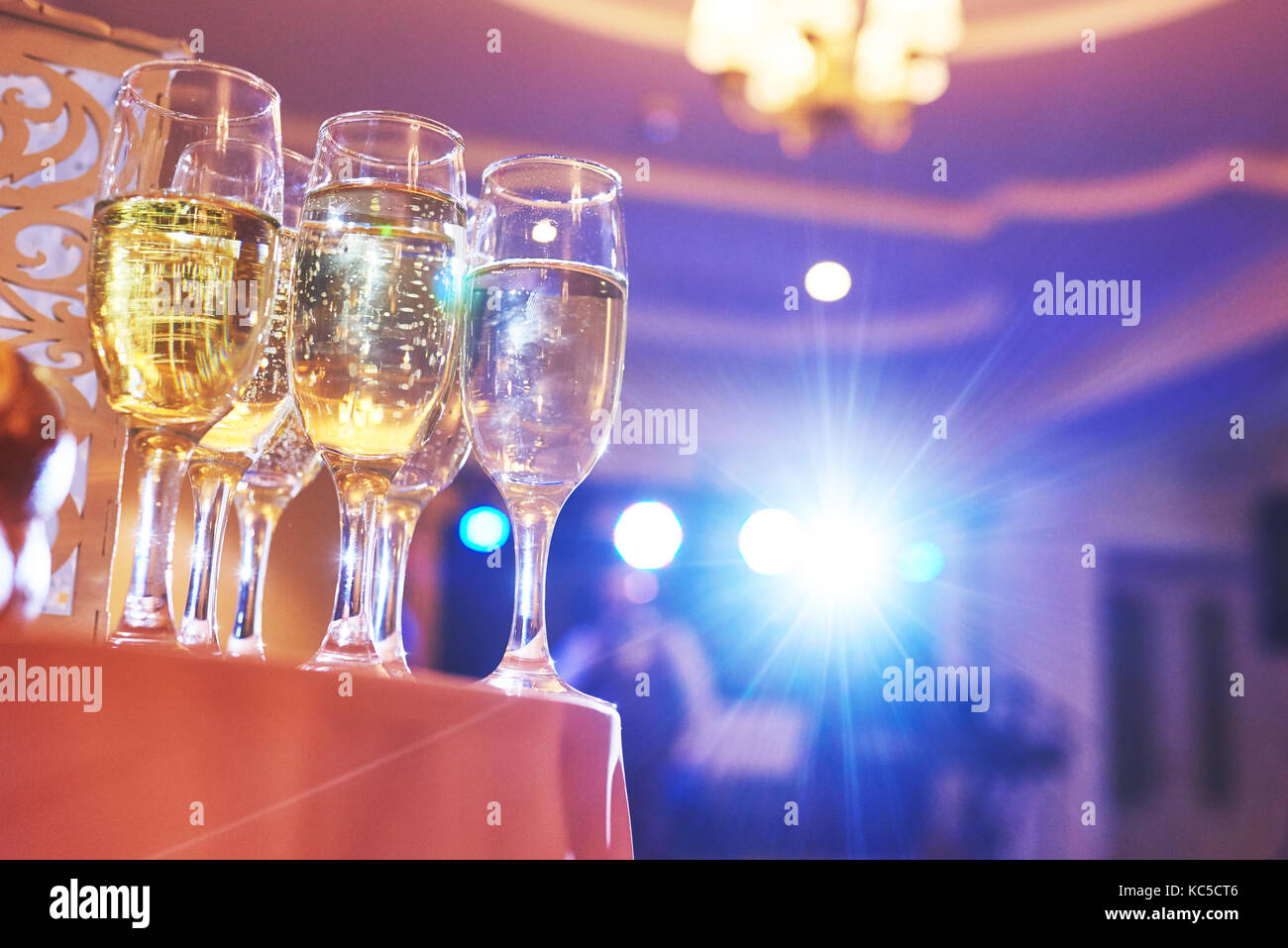 A lot of wine glasses in blue light with a cool delicious champagne or white wine at the bar - Stock Image