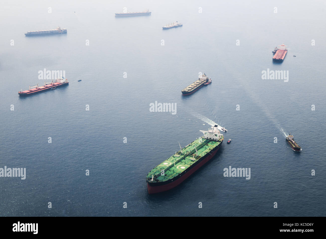 Ships in Straits of Singapore from the height. Big tanker with two helicopter platforms stay on anchor and wait - Stock Image