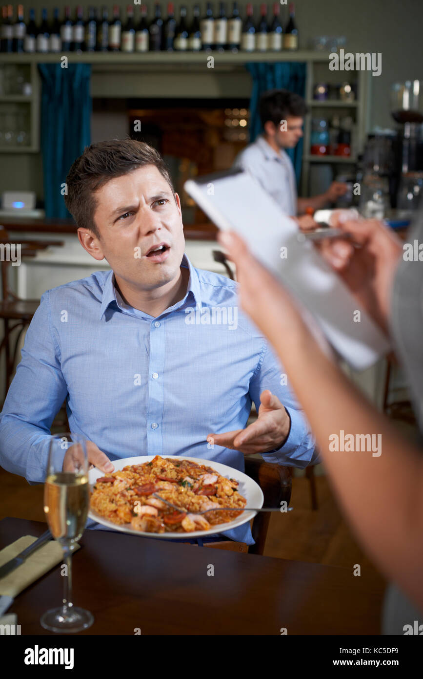 Customer In Restaurant Complaining To Waitress About Food - Stock Image