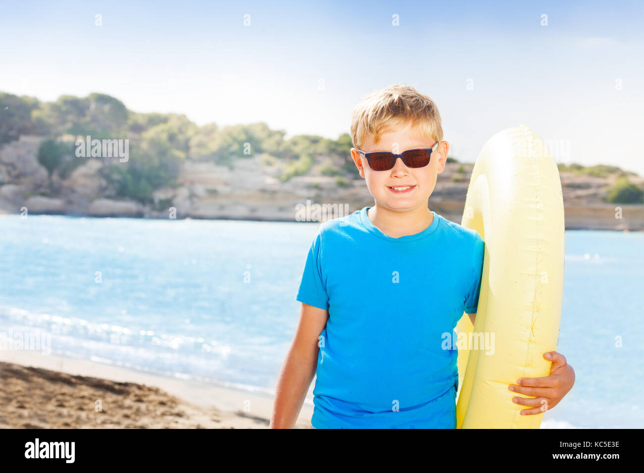 Cute preteen boy standing with inflatable ring on Mediterranean sandy beach - Stock Image