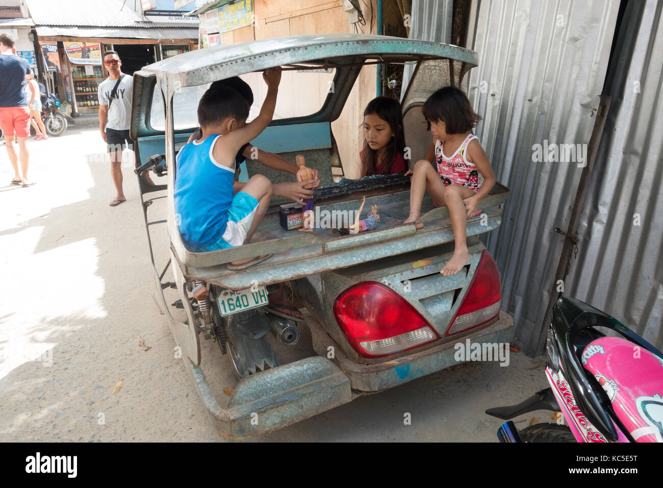 Philippines children playing with dolls  in the back of a taxi, Cebu city, Cebu, Philippines - Stock Image