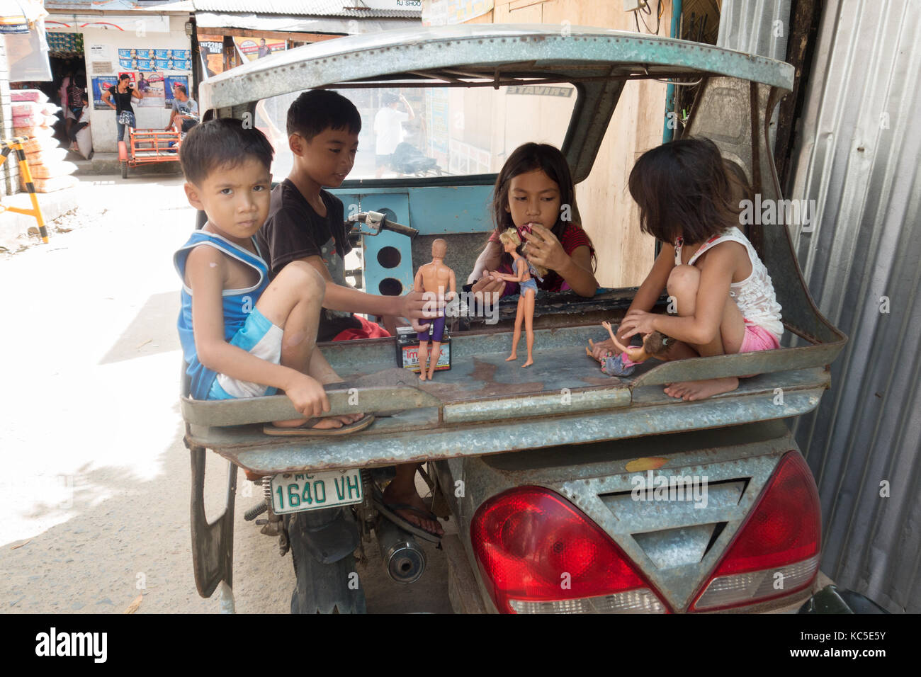 Filipino children playing with dolls  in the back of a taxi, Cebu city, Cebu, Philippines - Stock Image