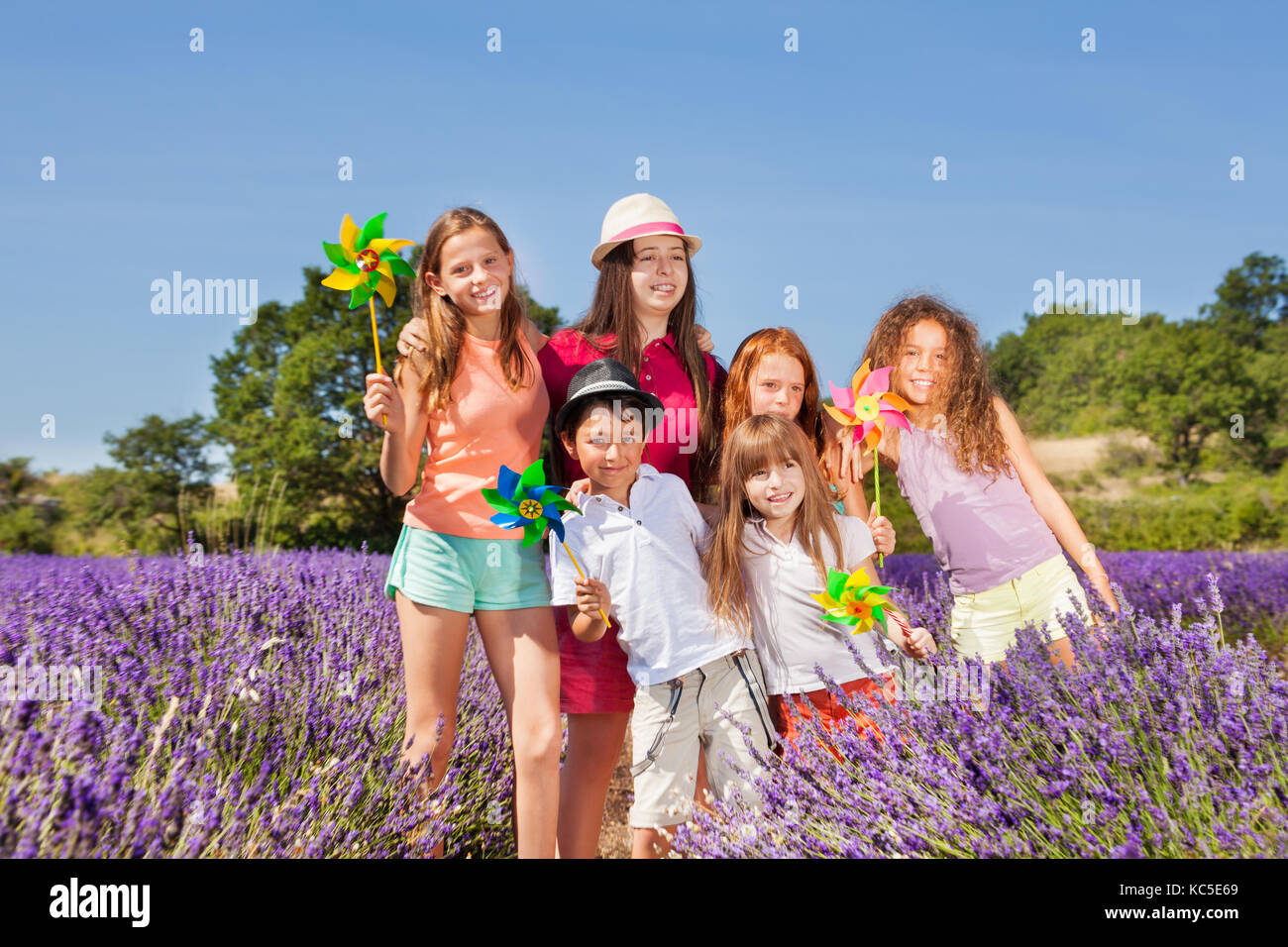Happy preteen boys and girls playing with pinwheels in lavender field - Stock Image