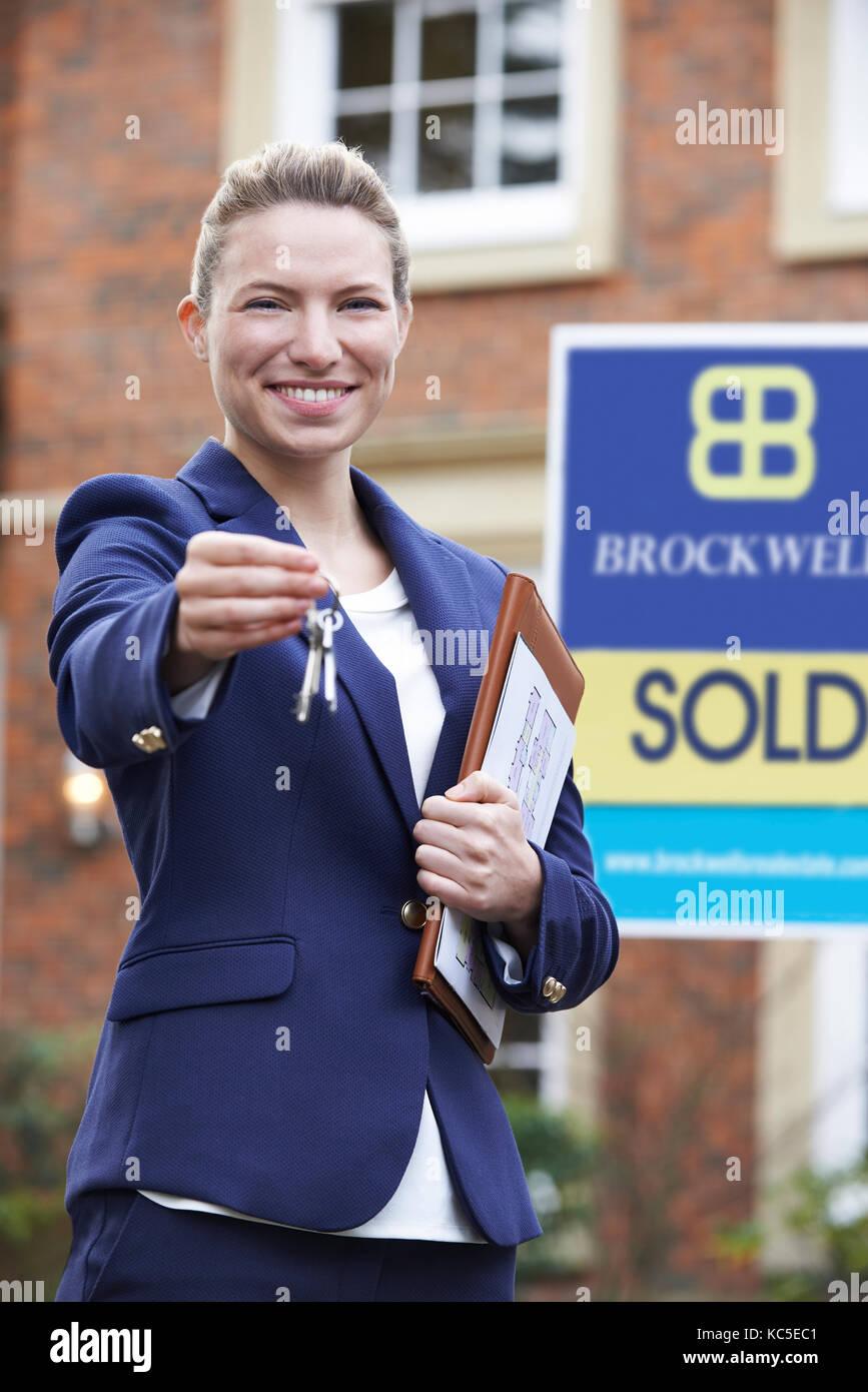 Female Realtor Standing Outside Residential Property Holding Keys - Stock Image