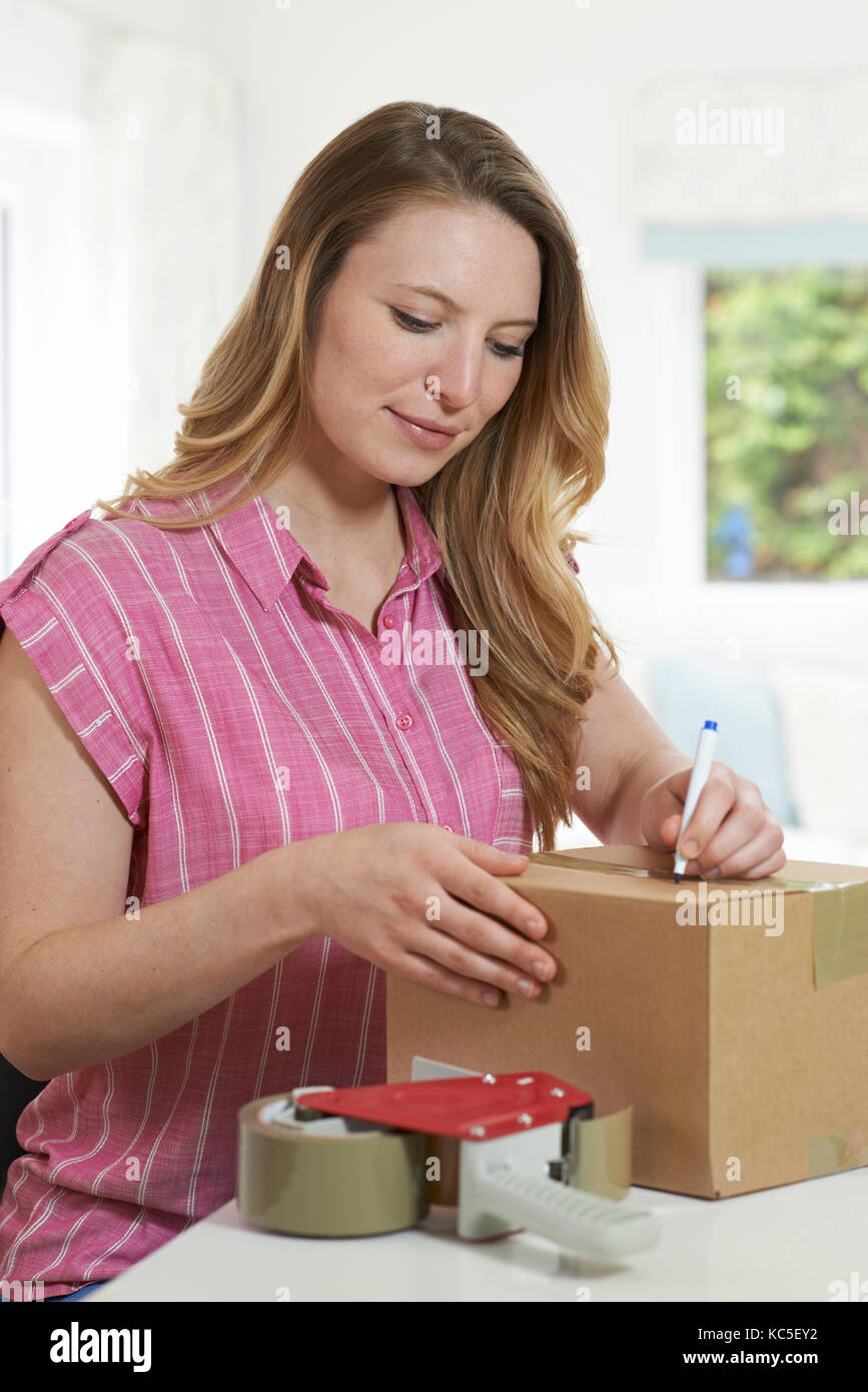 Woman At Home Writing Address On Package - Stock Image