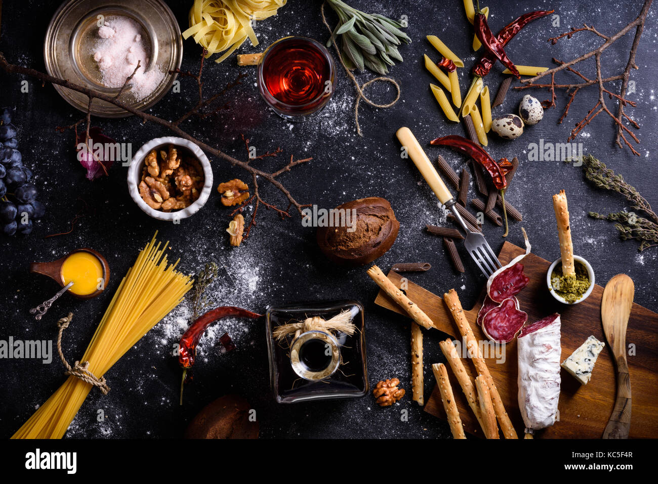 Appetizer, salami and cheese served with pasta and red wine on dark table. Italian cuisine ingredients. Top view. - Stock Image