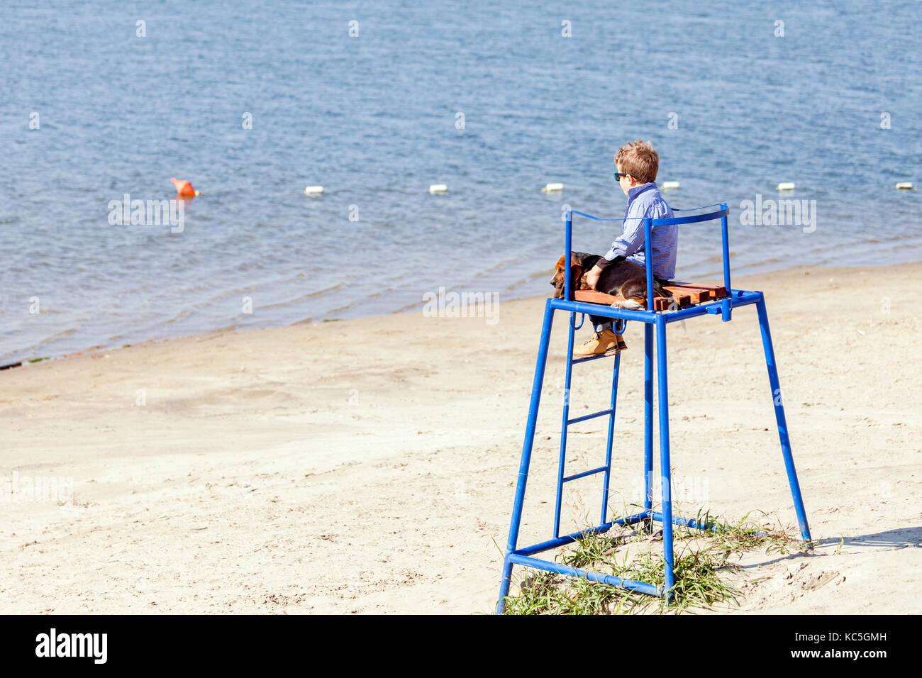 Little cute boy is sitting at the watchtower on the beach, next to the river with his puppy. They enjoy together - Stock Image