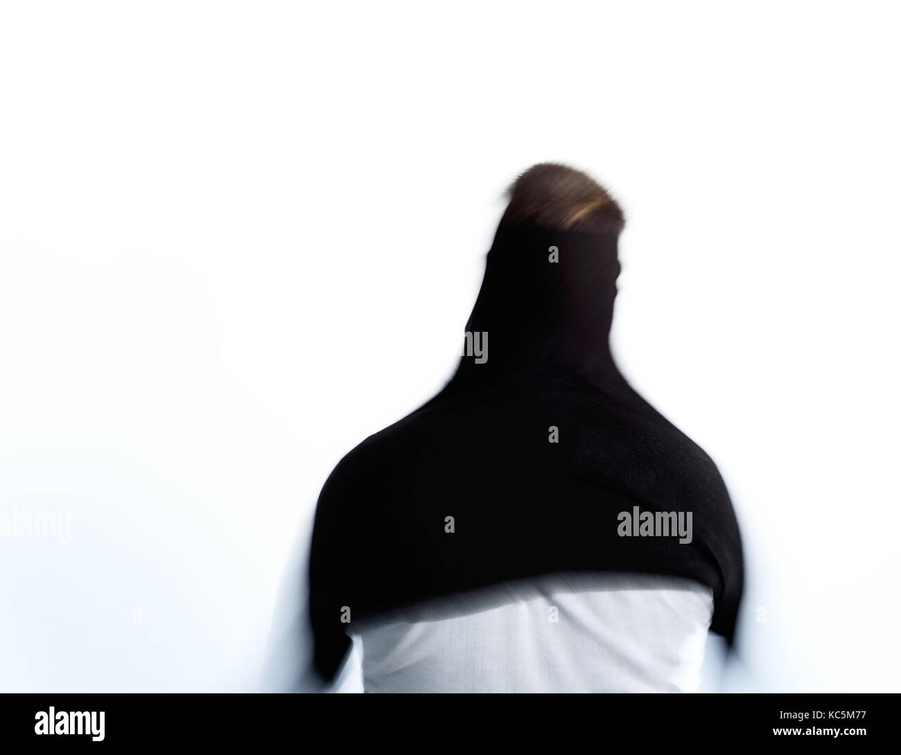 Man pulls on a black jumper in a blue with intentional blurring of the motion - Stock Image