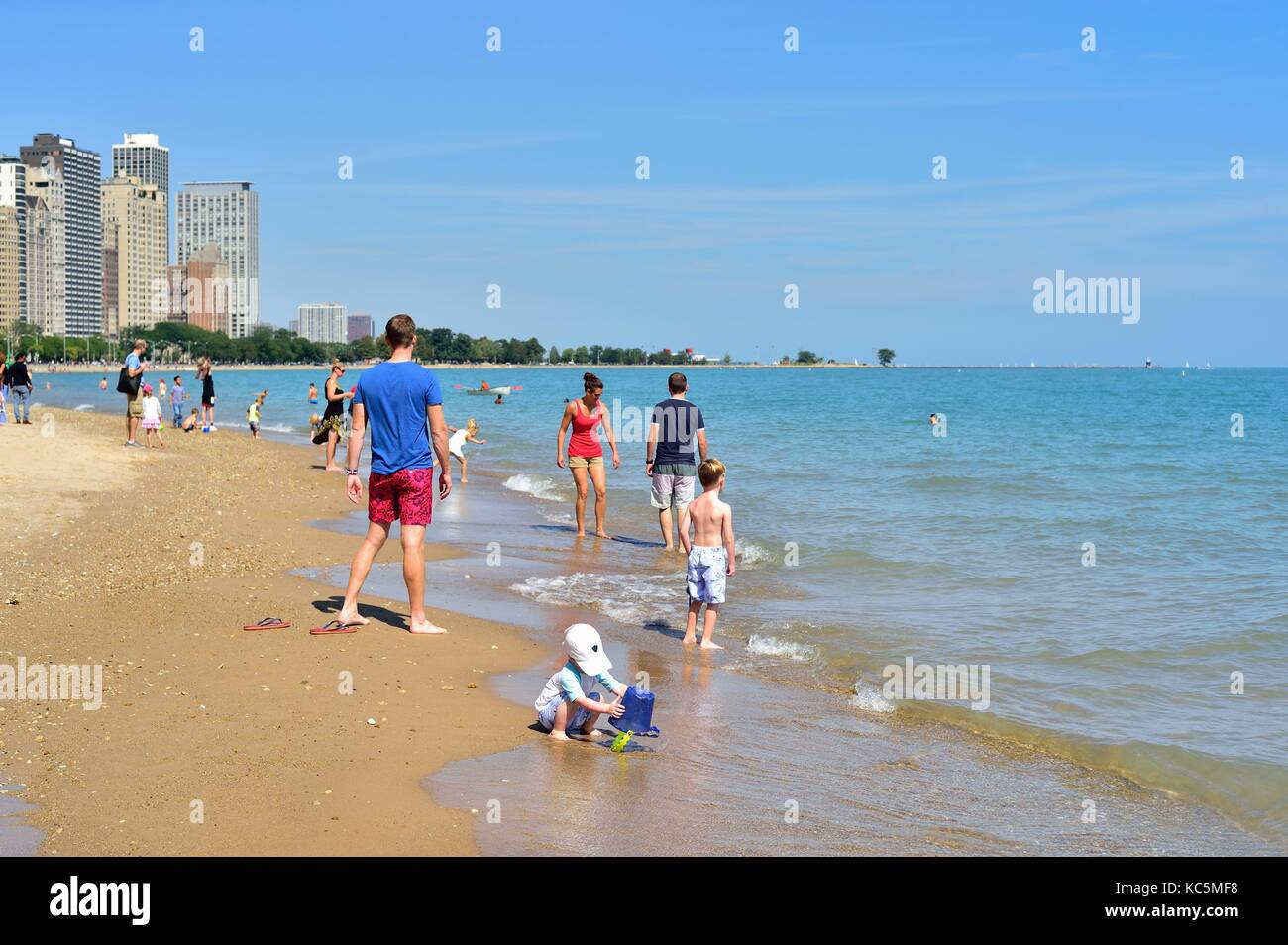 Young boy playing in the sand among people enjoying a summer day at Chicago's Oak Street Beach. Chicago, Illinois, - Stock Image