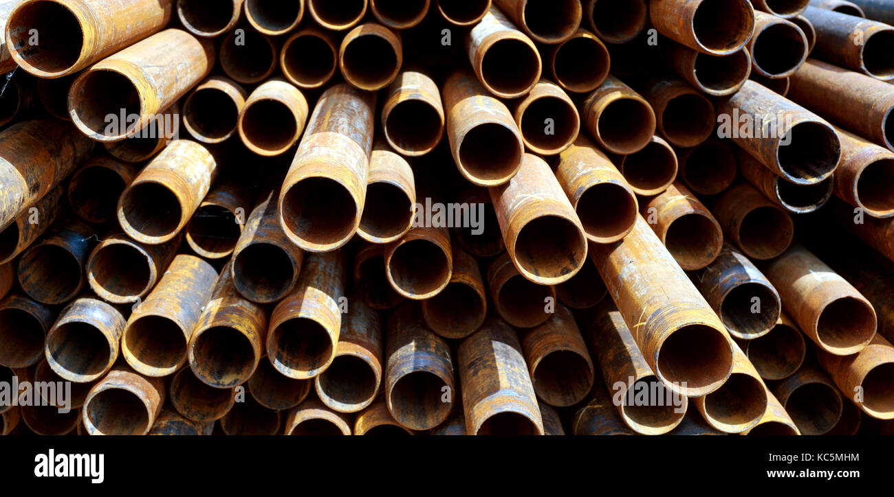Metal tubes and pipes stacked in a pile of different lengths creates abstract patterns with light and areas of shadows - Stock Image