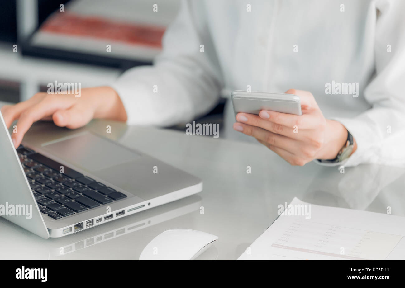 Close up businesswoman holding mobile phone and using laptop computer on office desk,Business communication concept. - Stock Image