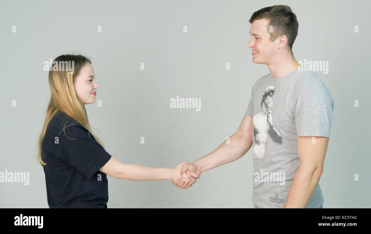 Young Man and young woman casual shaking hands and smiling on white background - Stock Image