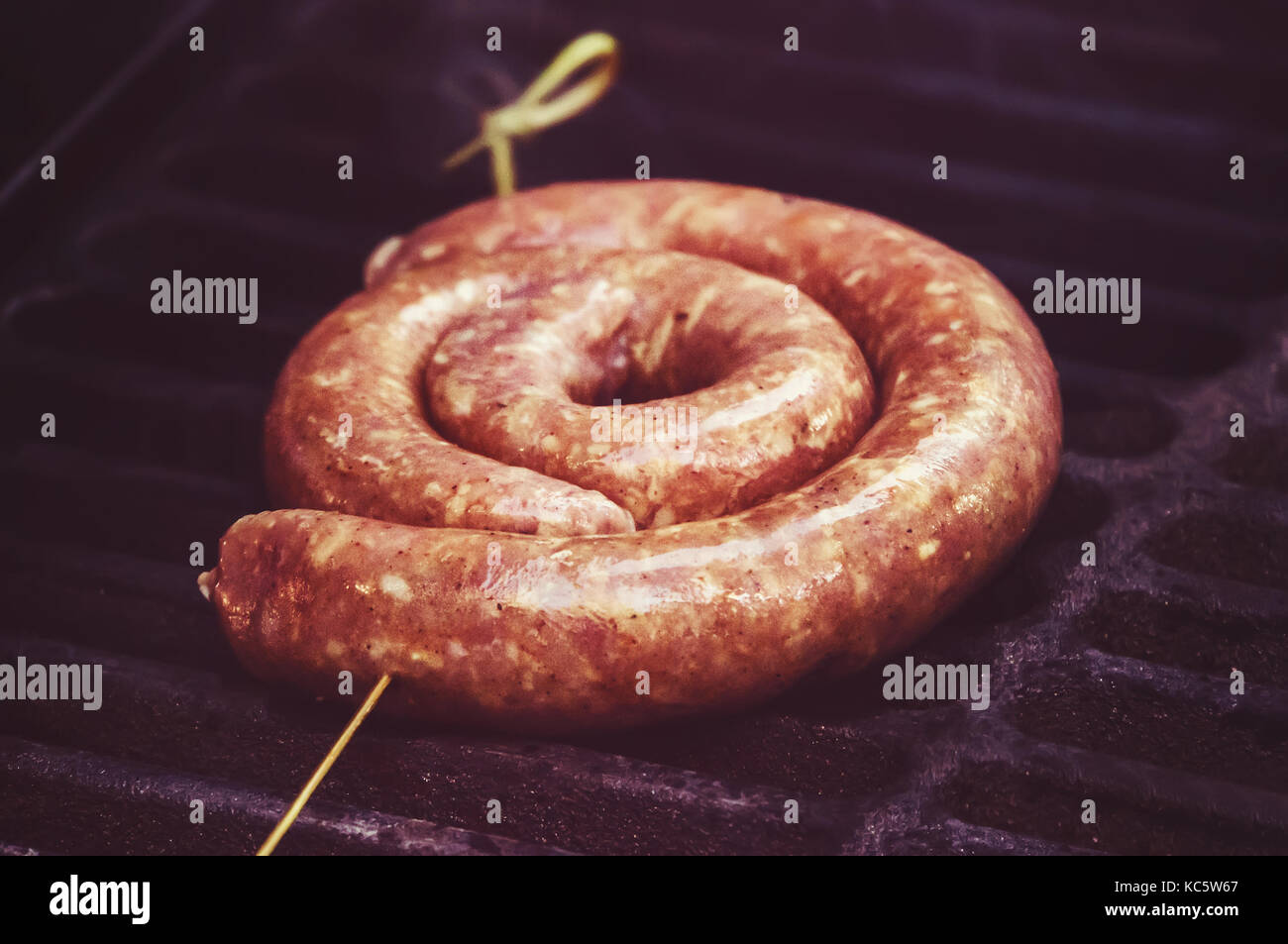 raw sausage links prior to cooking on a hot charcoal grill. fried German sausages. National cuisine. Ingredients - Stock Image