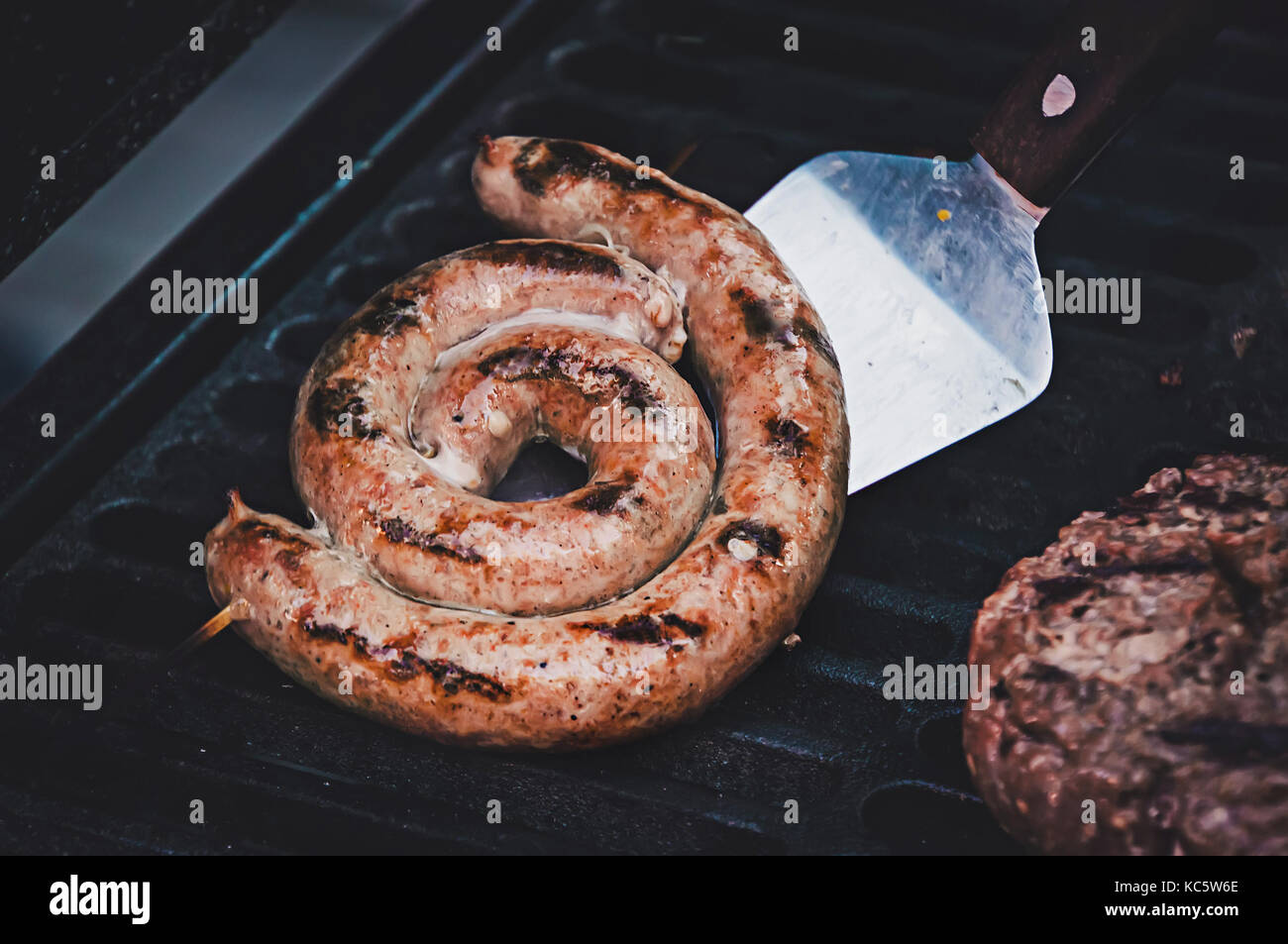 Grilled sausage with fresh rosemary on hot barbecue dish. the cook turns the frankfurter on the grill. Ingredients - Stock Image