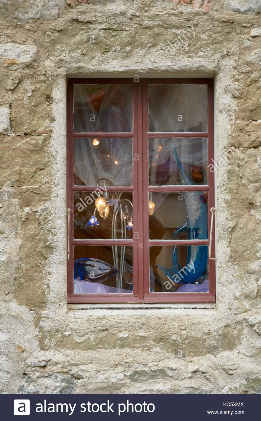 A brown wooden window frame with blue glass net curtains and lights on display Stock Photo