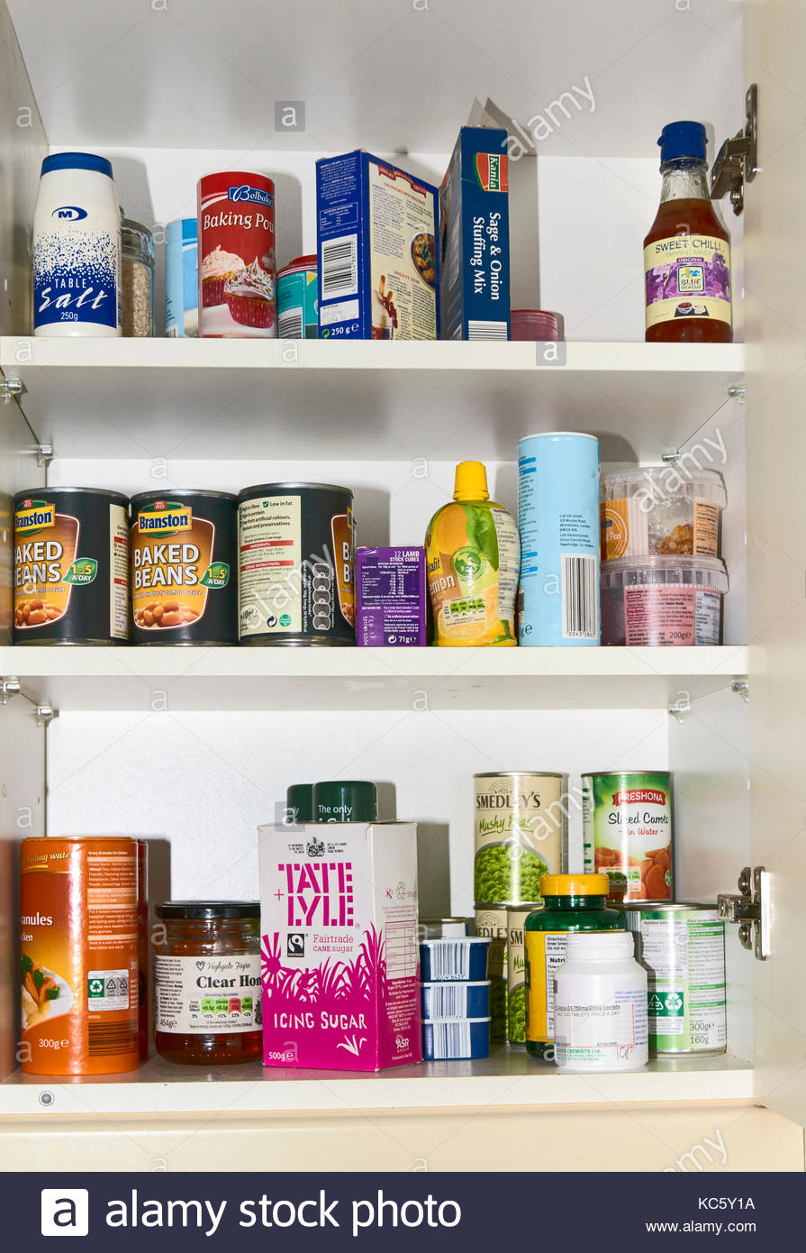 A typical food cupboard with tins packets and bottles of ingredients in a british uk home - Stock Image