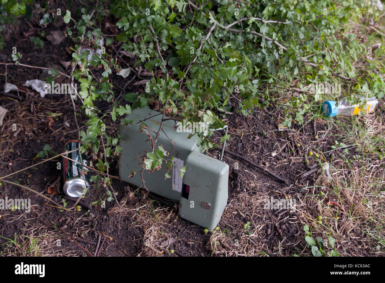 empty money safe abandoned under bushes with bits of litter, England Stock Photo