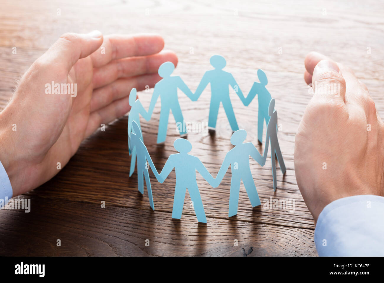 Close-up Of Businessperson Protecting Cut-out Figures On Wooden Desk Stock Photo