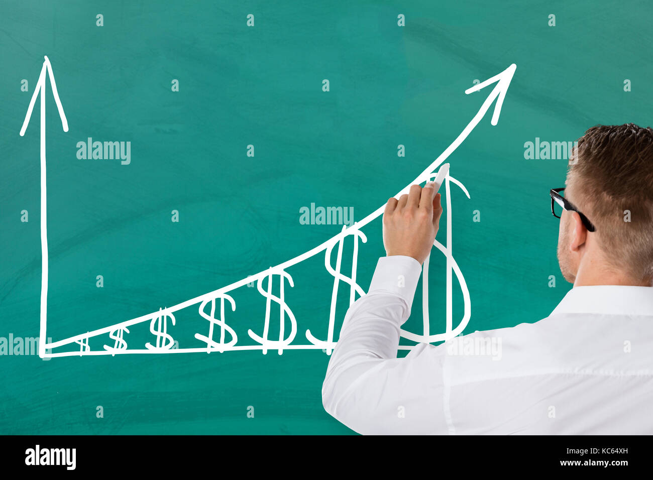 Businessman Showing Inflation Concept With Increasing Dollar Graph On Green Blackboard. Salary Growth Concept - Stock Image