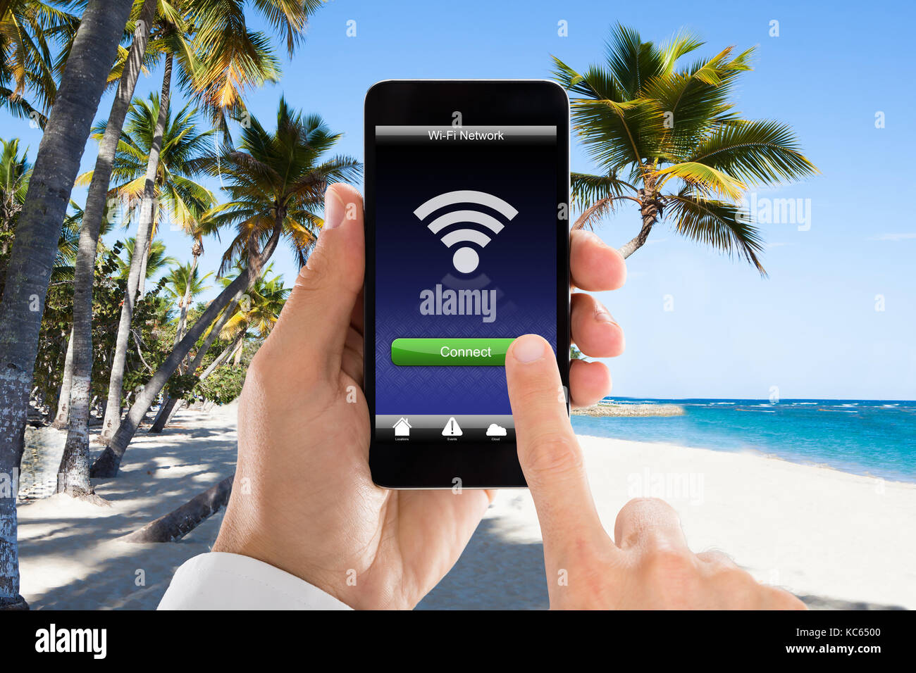 Close-up Of Man's Hand Connected WiFi On Mobile Phone At Beach. Internet Hotspot Coverage Concept - Stock Image