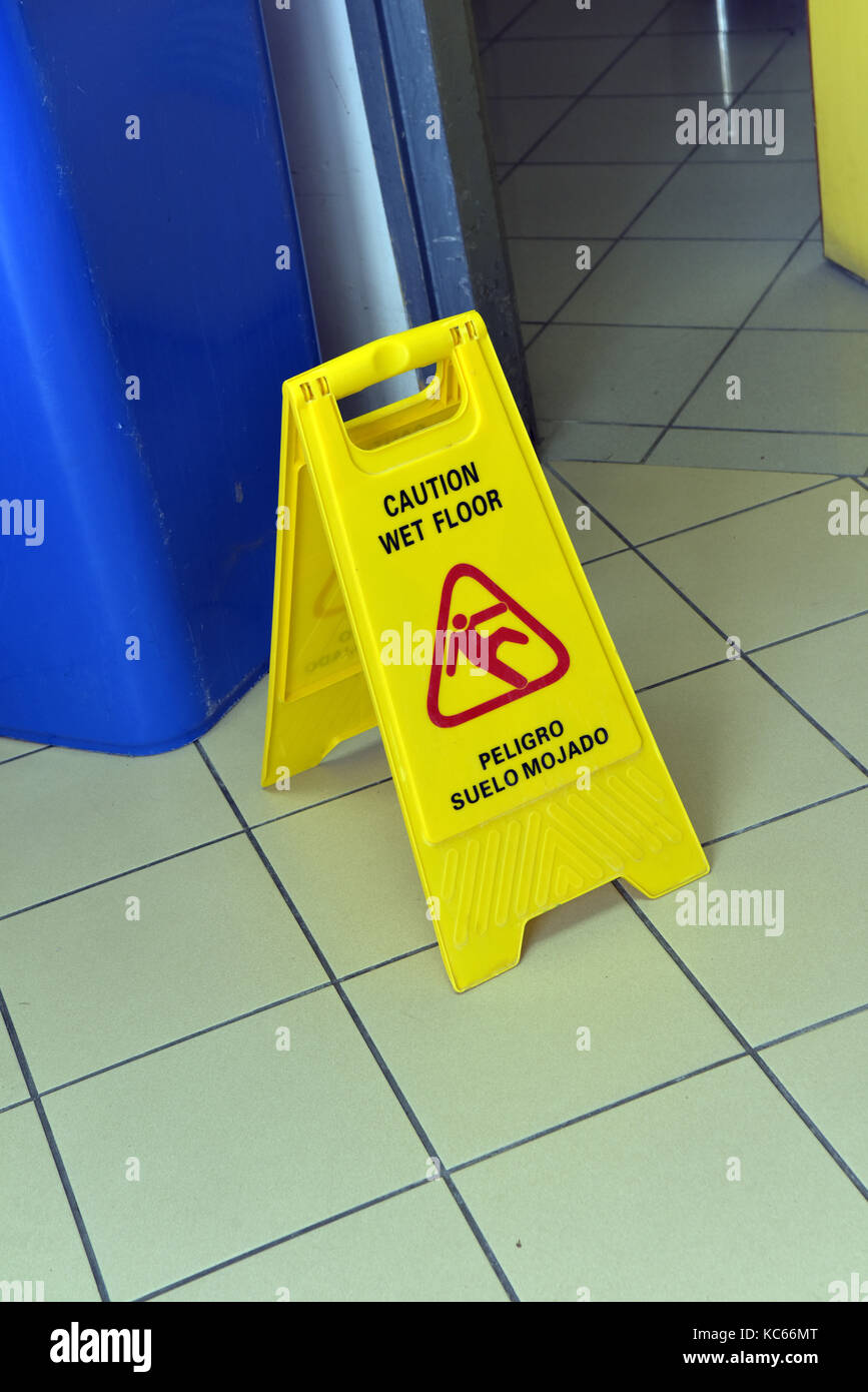 a cautionary warning sign for a wet floor warning of the risk of slipping on the wet surface or slippery tiles after - Stock Image