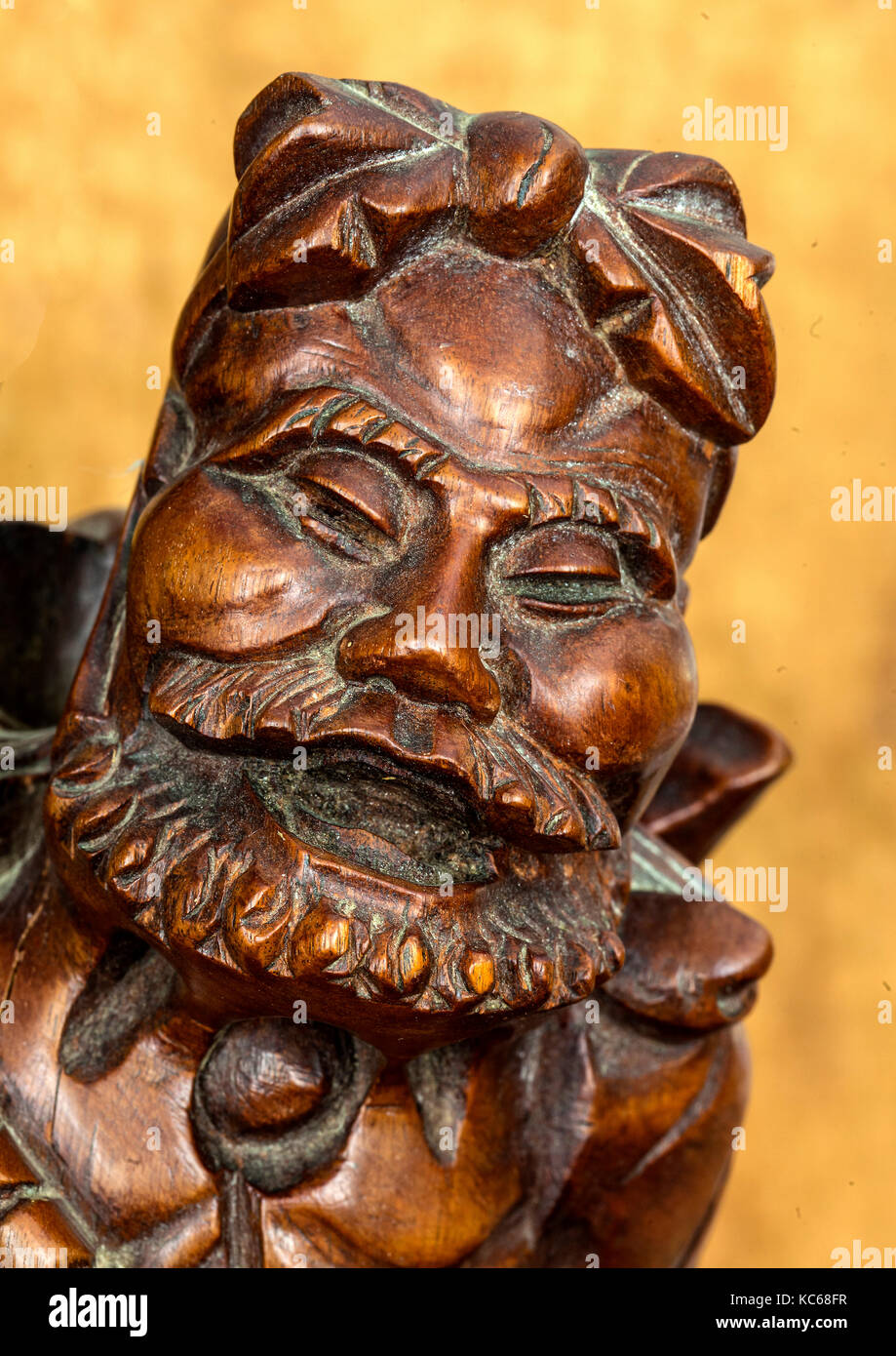 Antique statue of old Chinese man with eyes shut - Stock Image