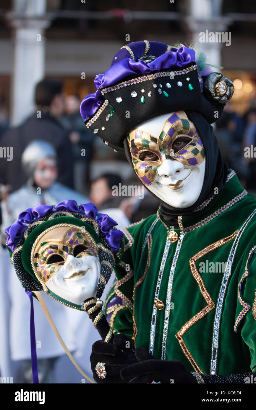 The Jolly Joker mask at the Carnival of Venice, Italy. Carnival dress with green and purple velvet, a hat with gems - Stock Image