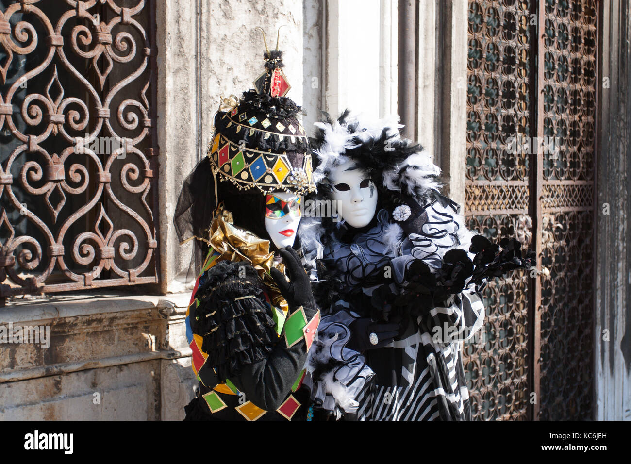 Couple of carnival costumes, with black and white plumes and coloured squares, from the Carnival of Venice, surrounded - Stock Image