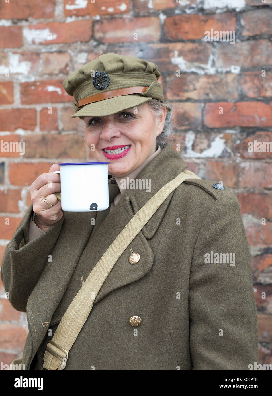 Lady dressed in British Army 1940's vintage uniform drinking tea from a tin mug. Welshpool UK 40's weekend - Stock Image