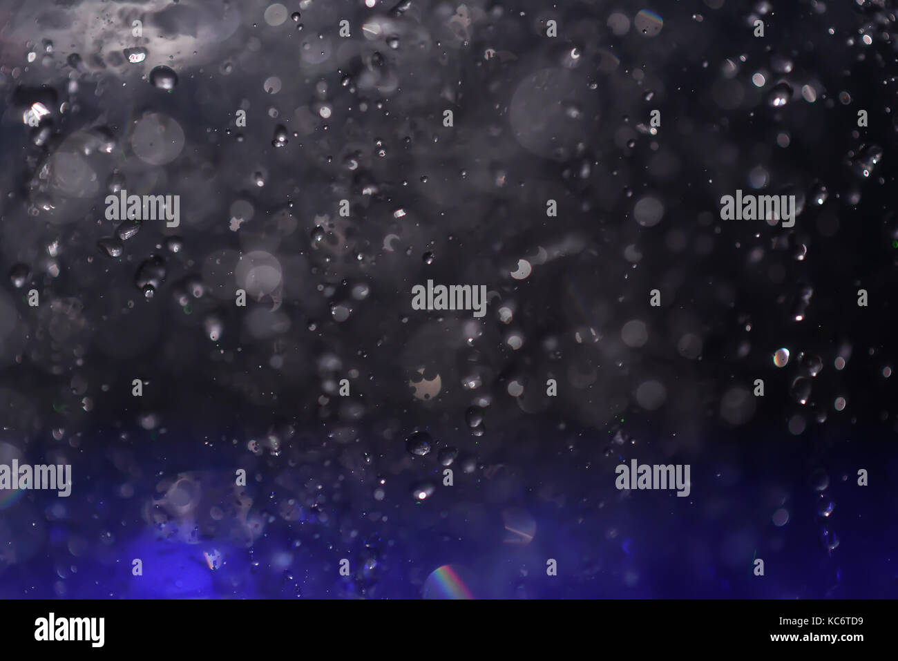 Multicolored spray fountain at night - Stock Image