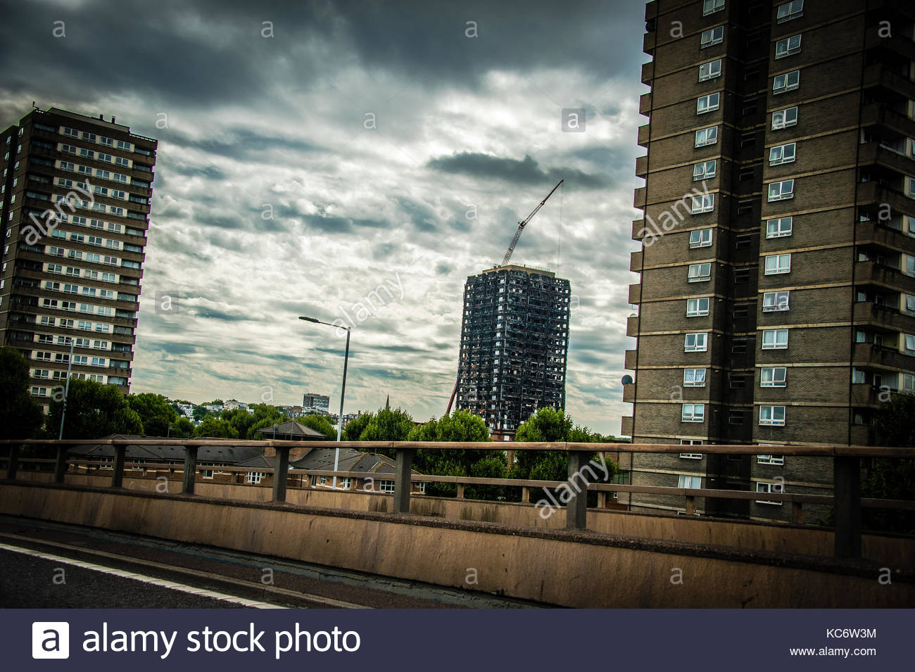 Grenfell Tower, scene of the fire tragedy, burnt flats seen from behind two other apartment blocks, view from the - Stock Image