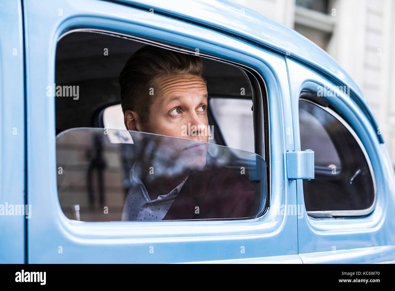 Man looking through window in retro car - Stock Image
