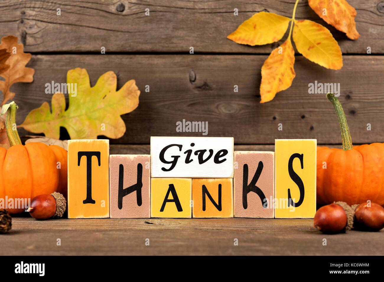 Give Thanks wood sign with pumpkins and leaves against a rustic wooden background - Stock Image