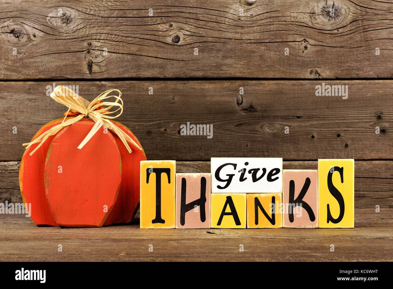 Shabby chic Give Thanks wood sign and pumpkin against a rustic wooden background - Stock Image