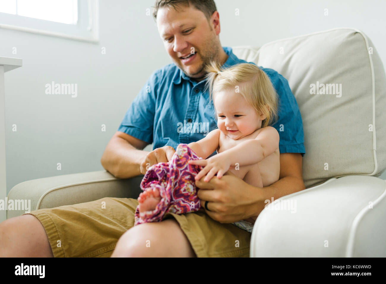 Father with baby girl (12-17 months) sitting in living room - Stock Image