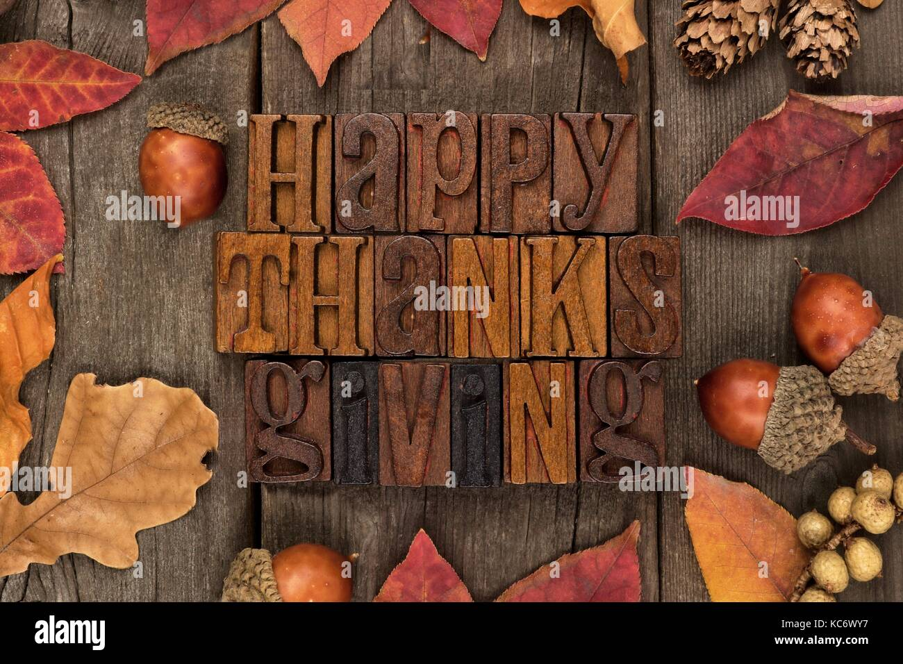 Happy Thanksgiving Spelled With Wooden Letterpress Frame Of Autumn Leaves Over A Rustic Wood Background