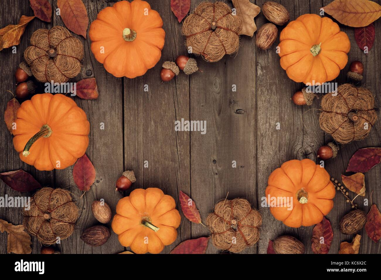Autumn Frame Of Pumpkins Leaves Nuts And Rustic Decor On An Aged Wood Background