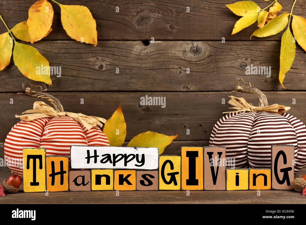 Happy Thanksgiving Wood Sign With Cloth Pumpkins And Leaves Against A Rustic Wooden Background