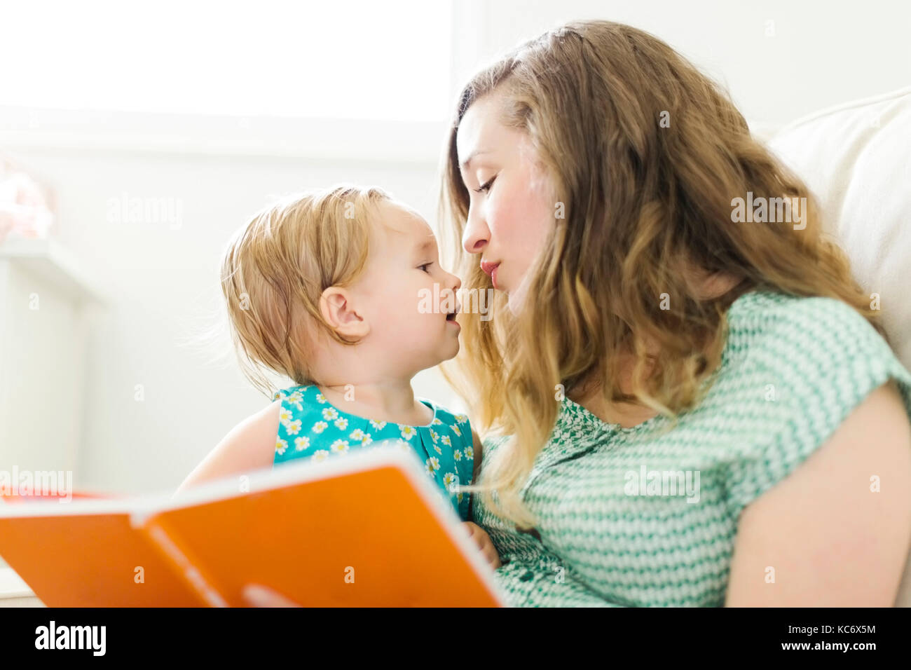 Mother with baby girl (12-17 months) sitting in living room and reading book - Stock Image