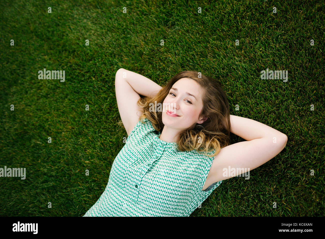 Portrait of woman lying on grass and looking at camera - Stock Image