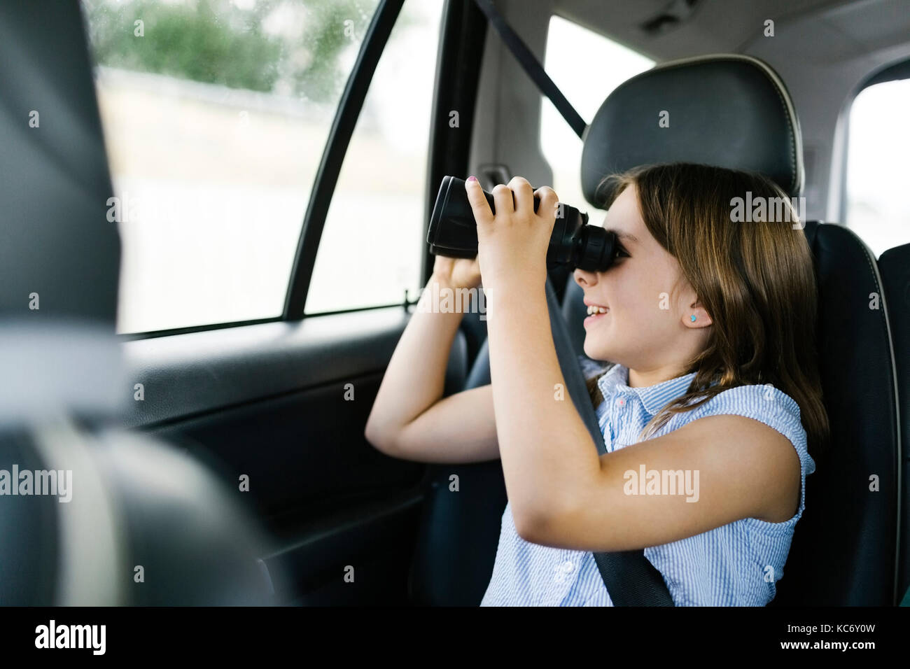 Girl ( 8-9) sitting in car and looking through binoculars - Stock Image