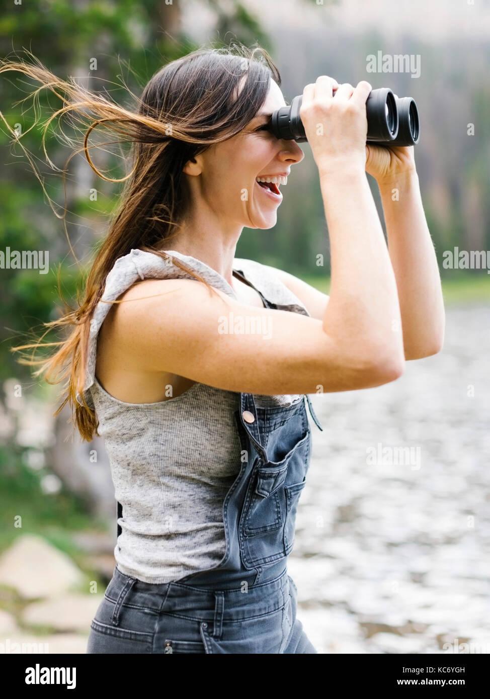 Woman using binoculars - Stock Image