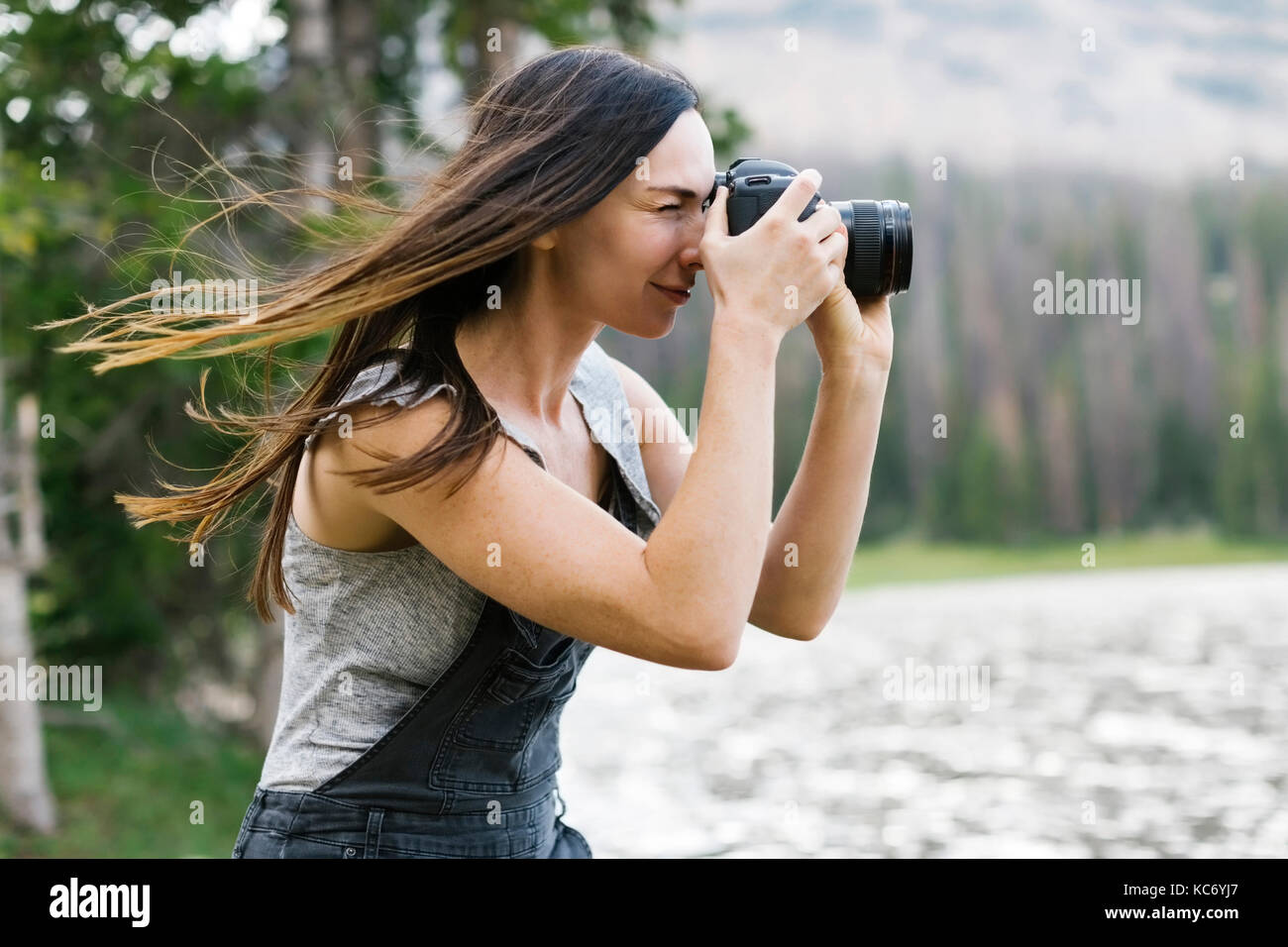 Woman taking pictures by lake - Stock Image