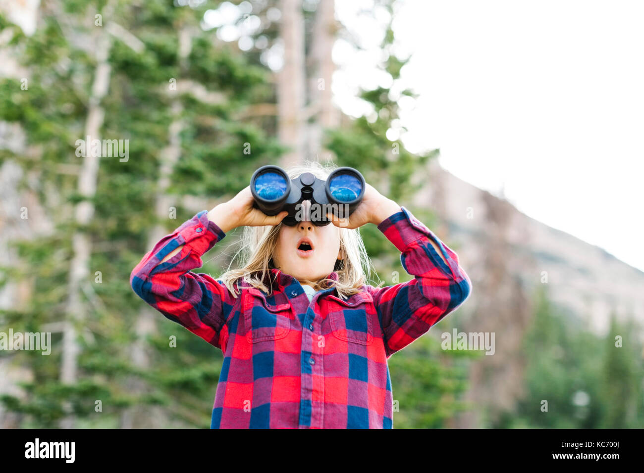 Boy (6-7) using binoculars in forest - Stock Image