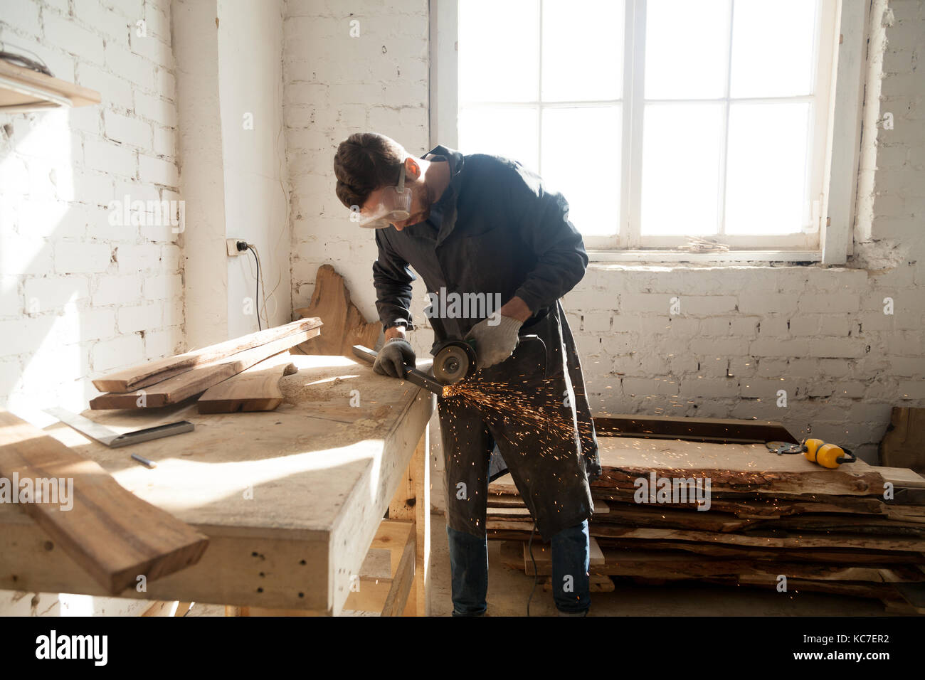 Man starting own small business in home workshop - Stock Image