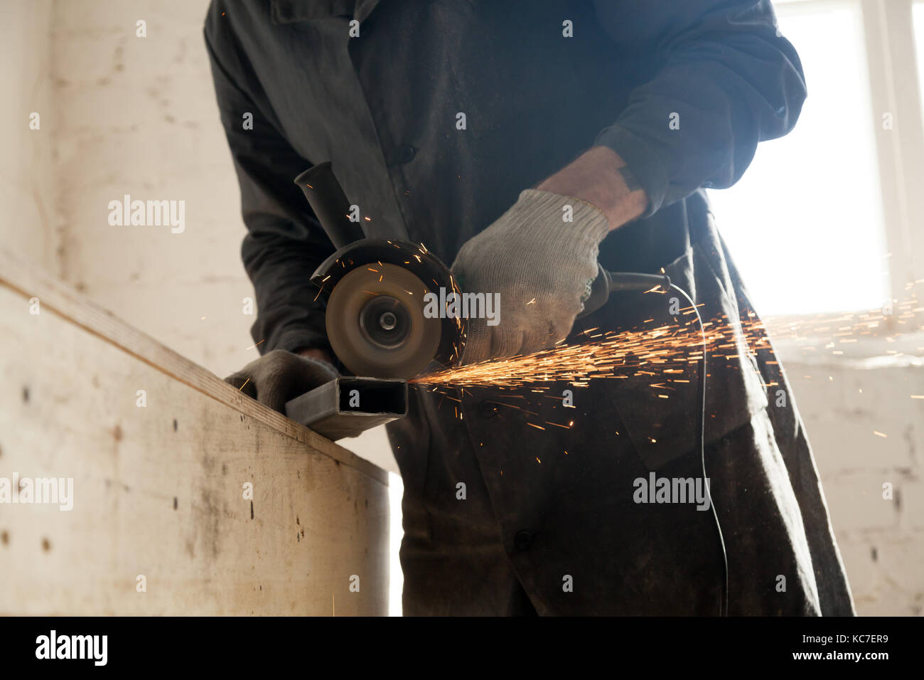 Close up of cutting metal pipe, man using angle grinder - Stock Image